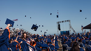 Graduates from Seaver College's Class of 2020 toss their hats at their commencement ceremony.