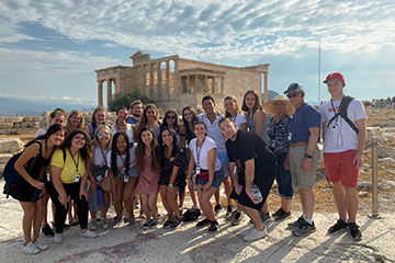 Group of students poses for a photo in front of ancient ruins