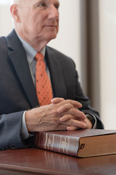 Marrs sits with hands folded over Bible