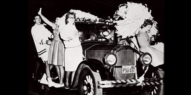 George Pepperdine College cheerleaders ride on an antique car during the 1960 homecoming celebration.