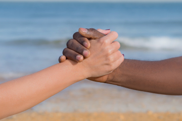 Diversity - people holding hands at beach