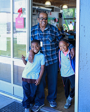Foster grandparent with two children at their school