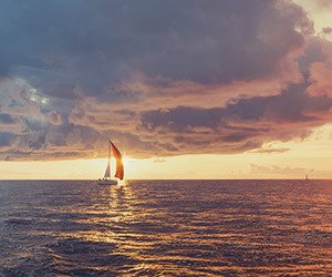 Harbor promotional image showing a lone sailboat sailing on the horizon at sunset