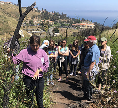 Karagan Smith showing surrounding group the resprout of the plant.
