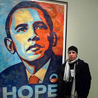 "Law student Mike Lebow stands next to the famous red, white, and blue ""Hope"" poster created by street artist Shepard Fairey"