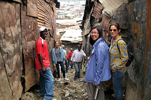 Professors Loan Kim and Donna Plank stand amid trash and sewage in a residential area in Mathare Valley, the second largest slum in Nairobi.