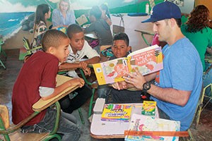 A Project Serve volunteer reads to students at The Good Samaritan in the Dominican Republic.